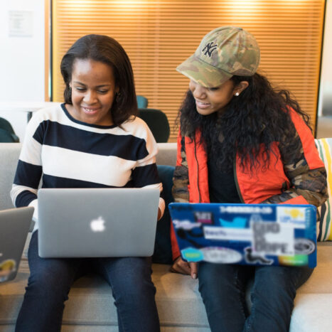 two women on couch with laptops